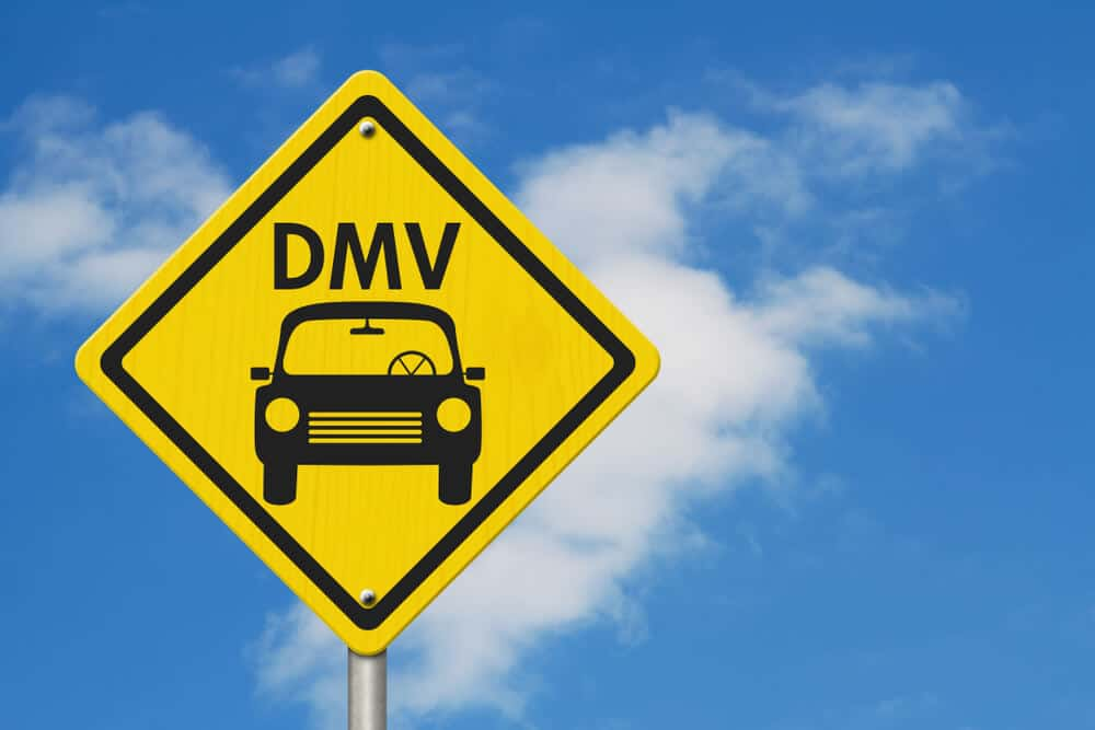 yellow road sign that reads DMV