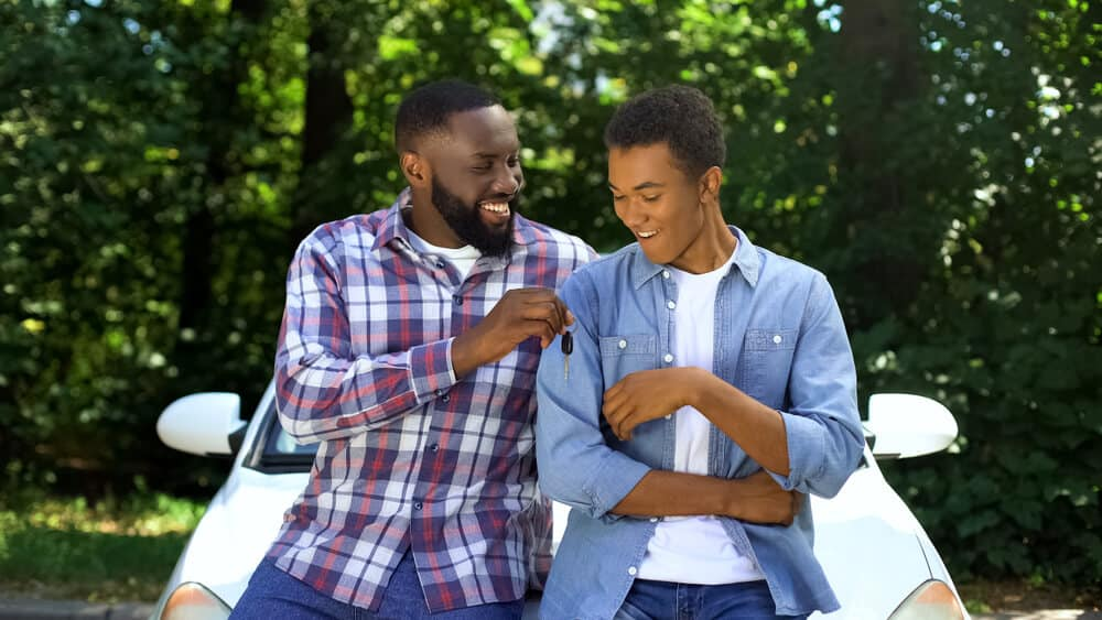 Happy dad giving car key to son with car insurance for teenagers