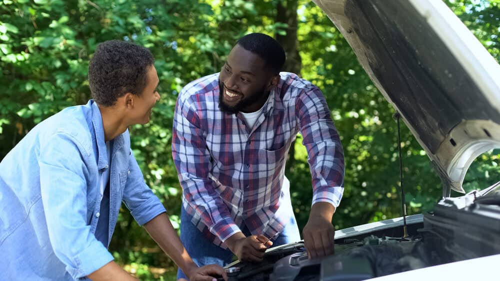 Father explaining car structure to son and smiling with car insurance for teenagers