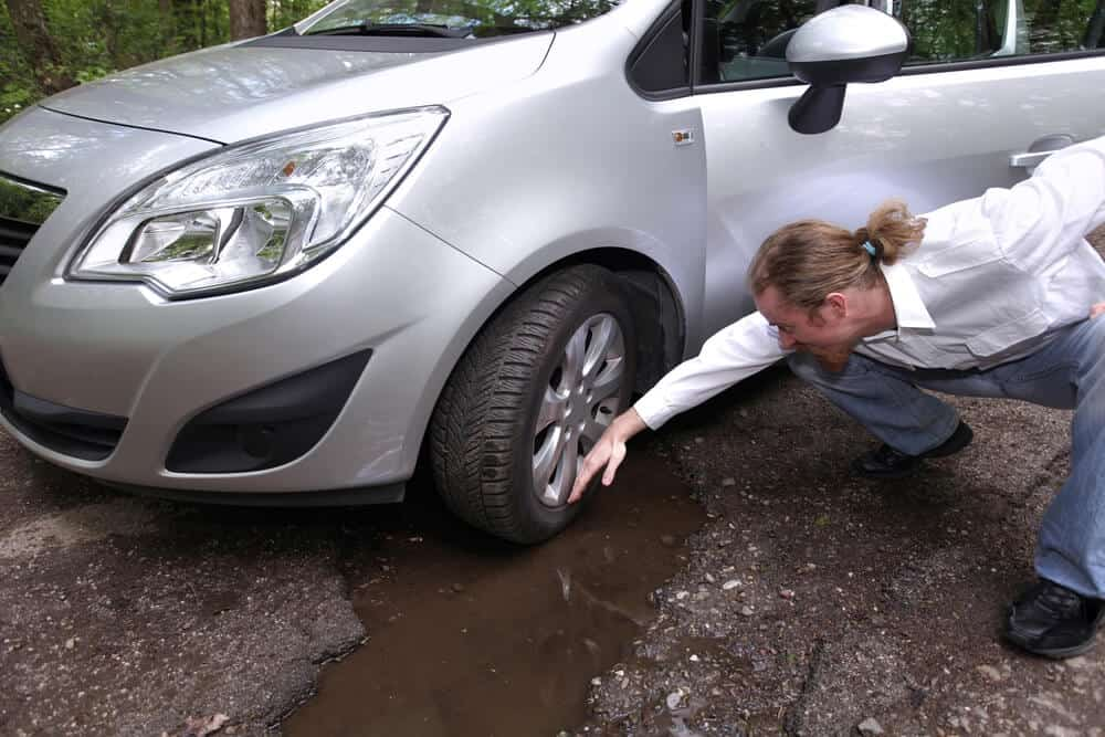 man checking the damage on his tires because he didn't avoid a pothoe