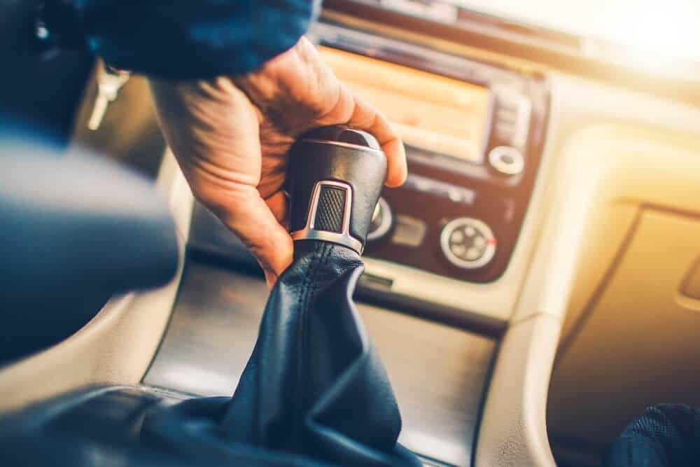 hand changing gears on a stick in a manual transmission vs automatic