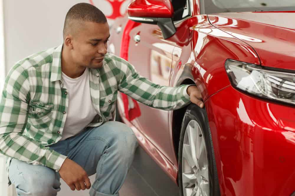 african american man checking tire pressure with no gauge on a red car