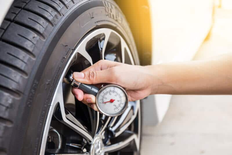 hand with tire pressure gauge checking wheel
