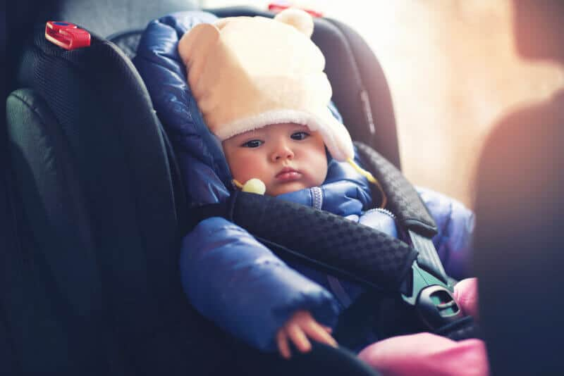 small baby riding inside a car in seat