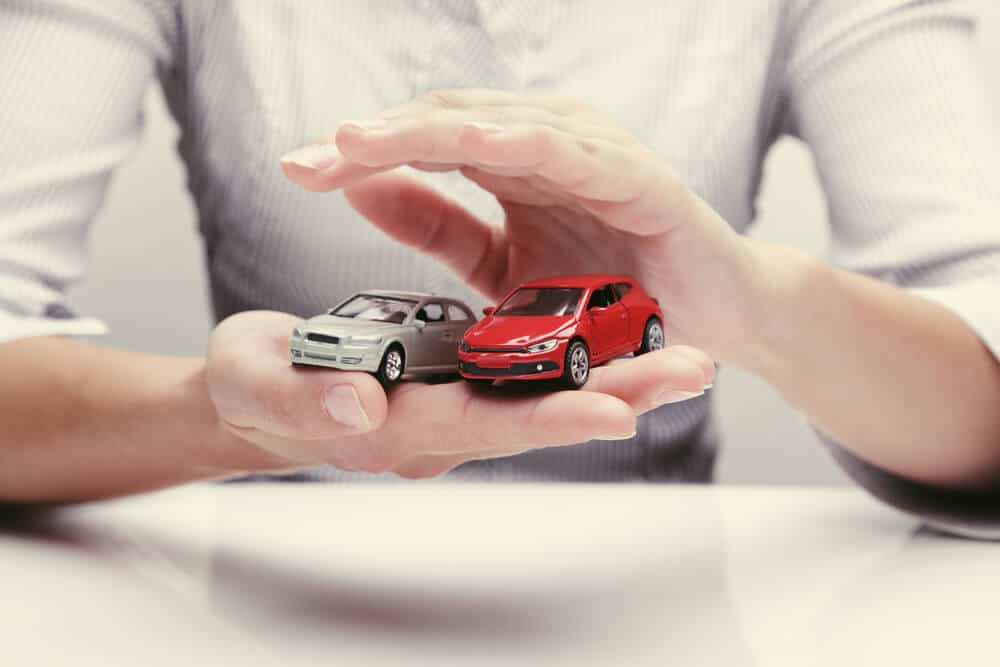 hands holding two toy cars to symbolize multiple car insurance