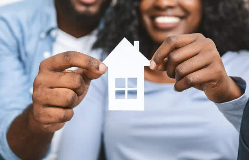 african american couple holding a paper house to simbolize they are renting for the first time