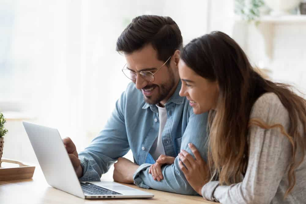 happy couple with laptop finding cheap car insurance