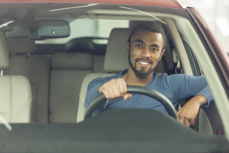 happy african american man in red car drivers seat
