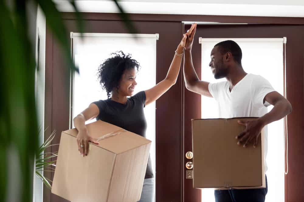 happy african american coulpe high fiving when renting for the first time