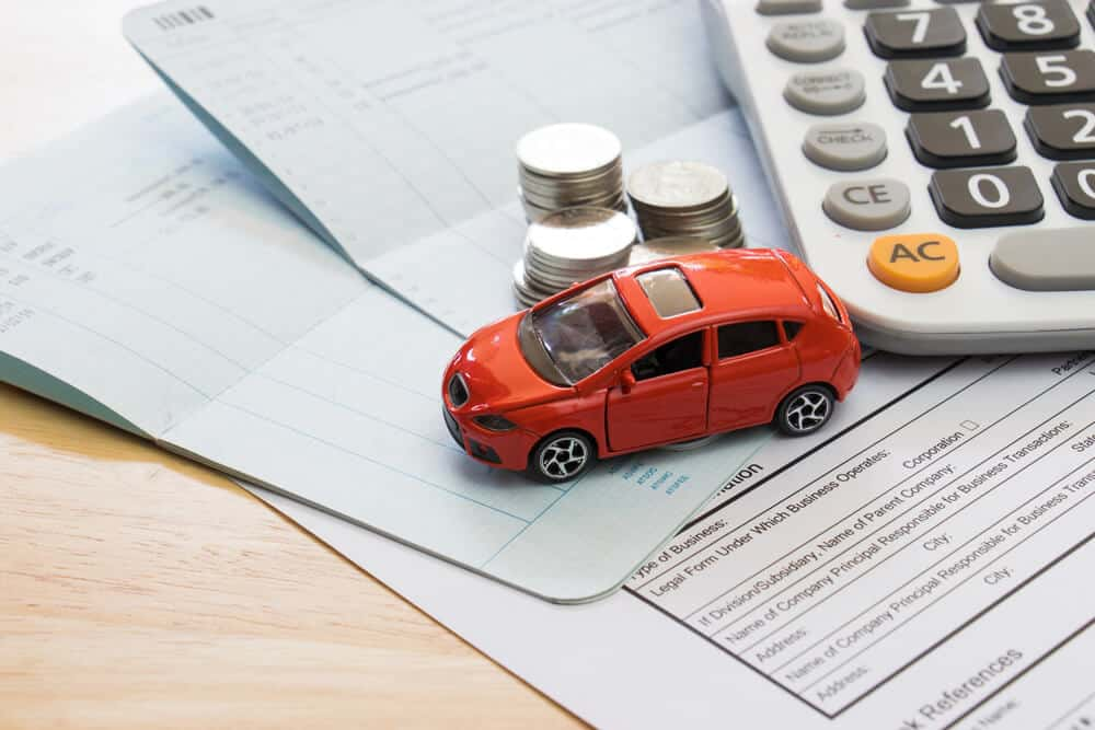 toy car on top of papers and coins to symbolize car insurance