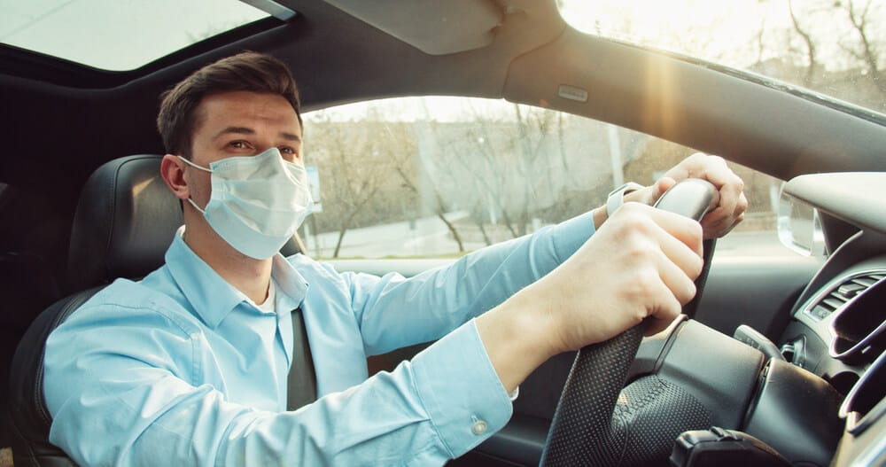 young man driving a car with mask during covid 19