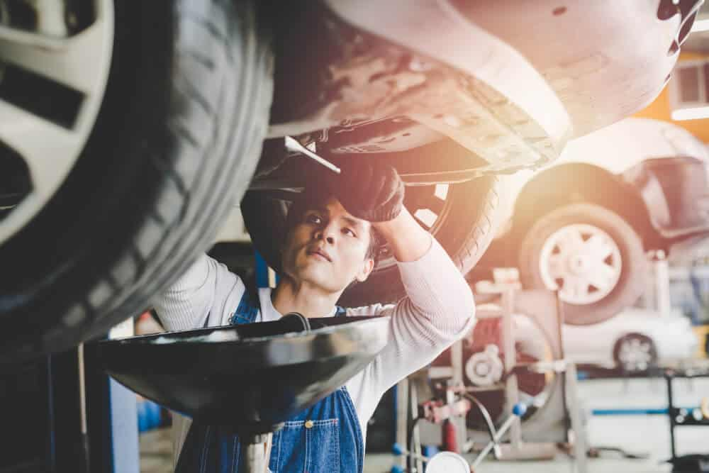 young mechanic changing a cars oil
