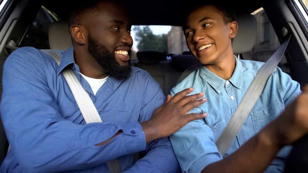 Smiling african american father praising teen son for driving well in alabama
