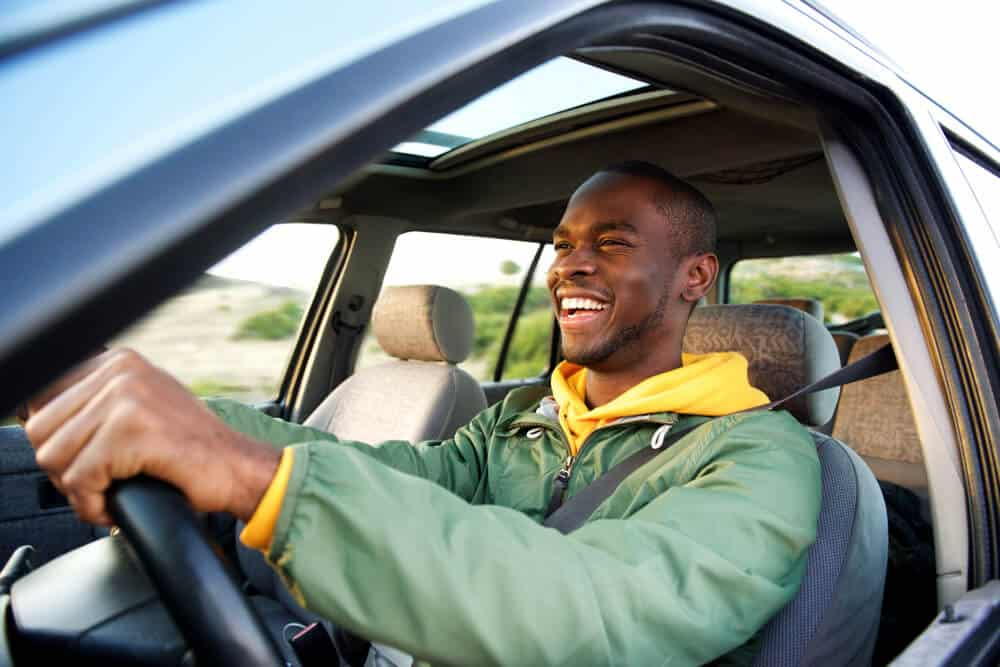 side view of african american young man driving car smiling