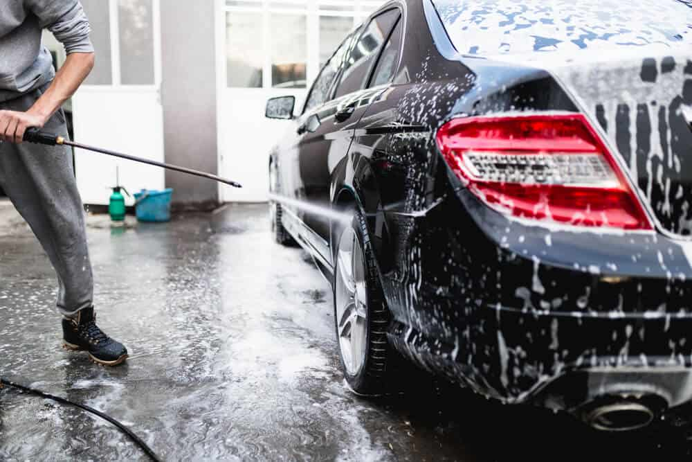 man Cleaning Car Using High Pressure Water