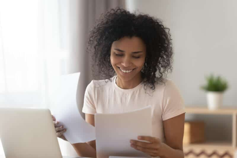 happy african american woman looking at car insurance policy