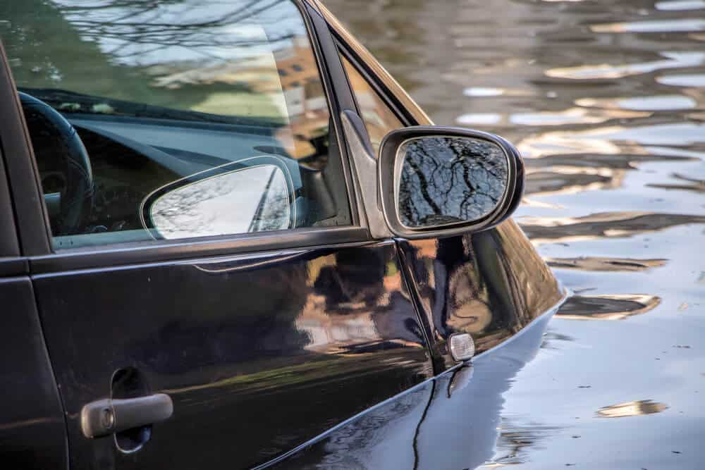close up of car submerged in water during severe flood