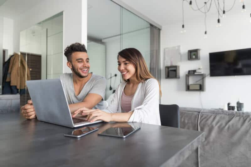 couple in table with laptop looking at how much is car insurance