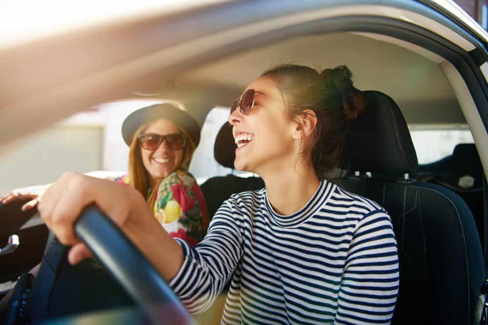 two happy women in car with an insurance policy