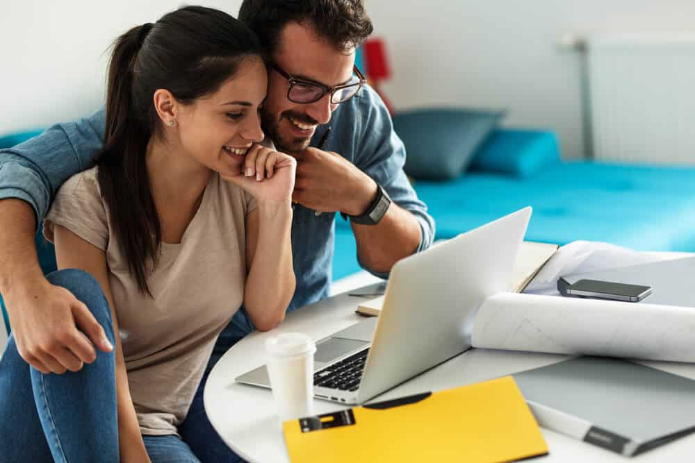 happy couple in laptop buying car insurance online