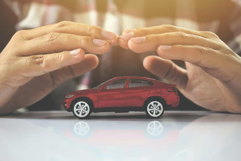 hands over toy car to represent car insurance