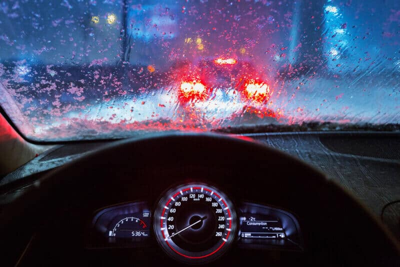 view from a cars drivers seat with rain and traffic in the windshield