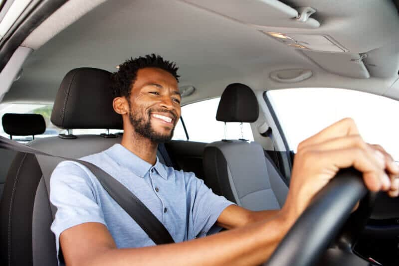 smiling african american man driving a car