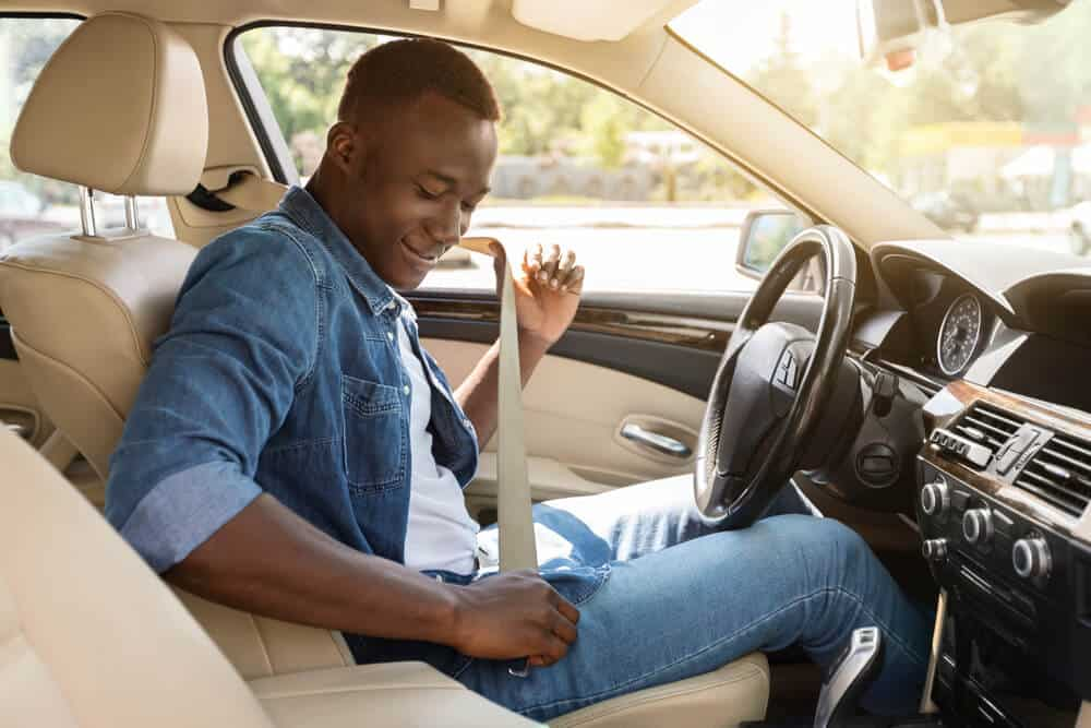 african american man in cars drivers seat putting on seatbelt