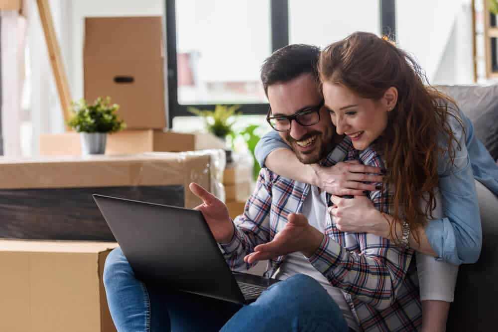 couple in new home looking at laptop