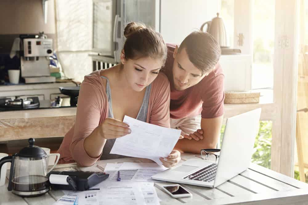 couple in kitchen looking at car insurance bills in their kitchen