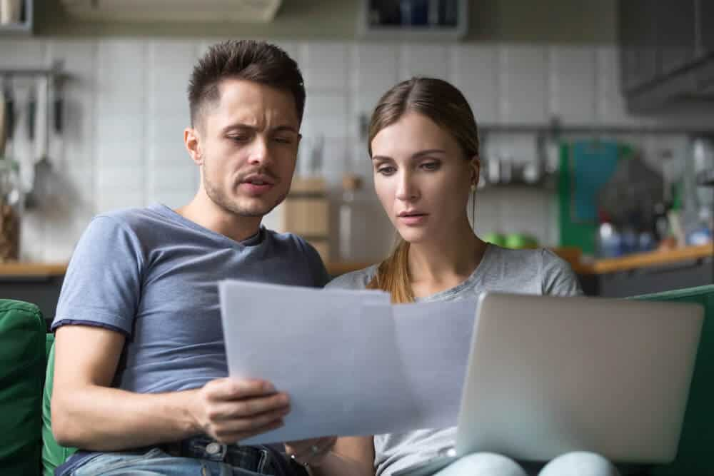 Serious couple checking bills with papers and laptop