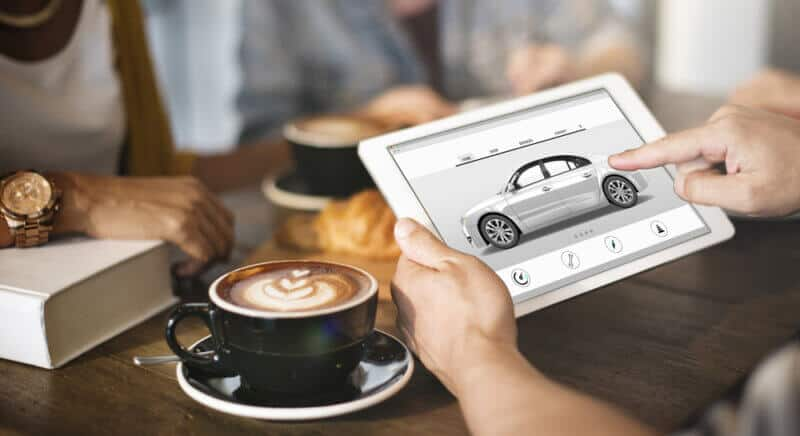 person with tablet shopping for new car with insurance