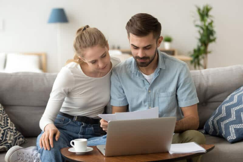 couple in couch looking at renters insurance paper in alabama