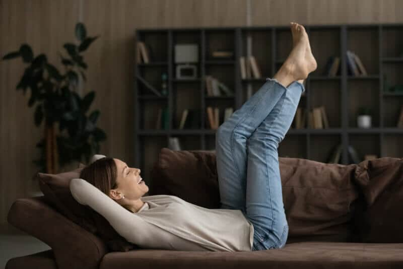 relaxed young woman in her couch with feet up