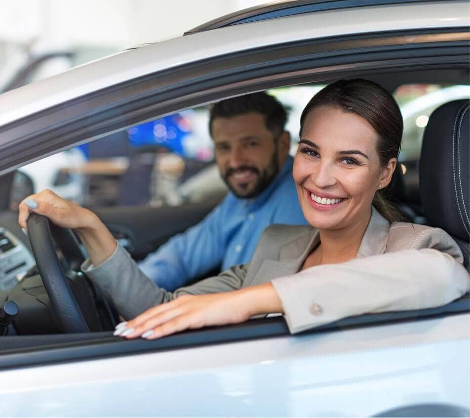 Smiling couple sitting in car looking out driver's side window