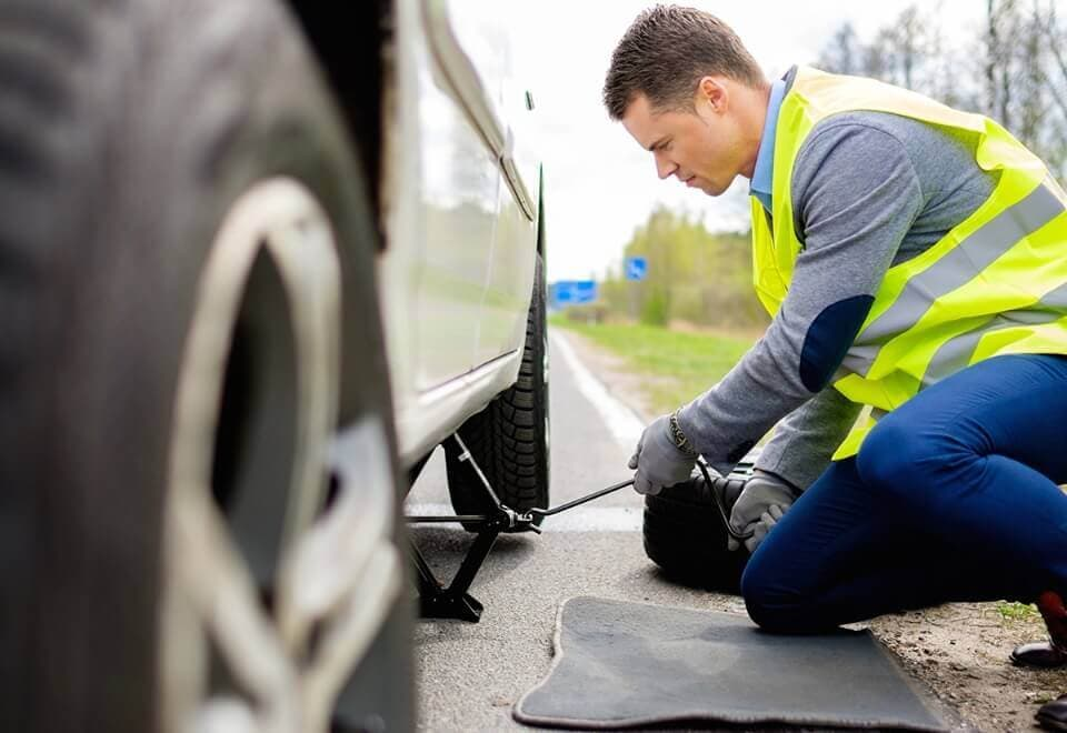 Roadside assistance technician changing flat tire on the side of the road