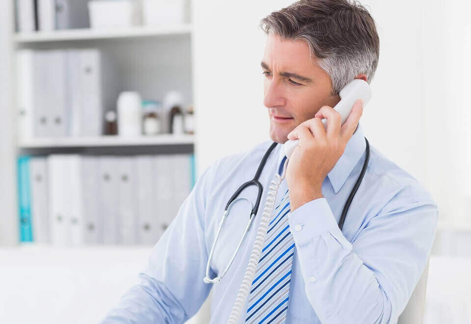 Mature male doctor in his office using a computer while talking on the phone to a patient